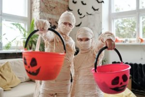 two children dressed as mummies holding trick or treat baskets in living room